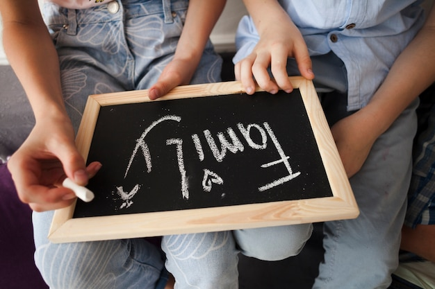 Midsection of children holding chalk and slate with family text