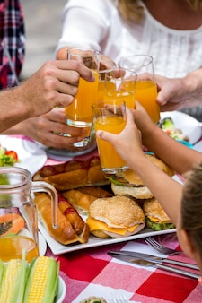Midsection of family toasting drinks while having lunch