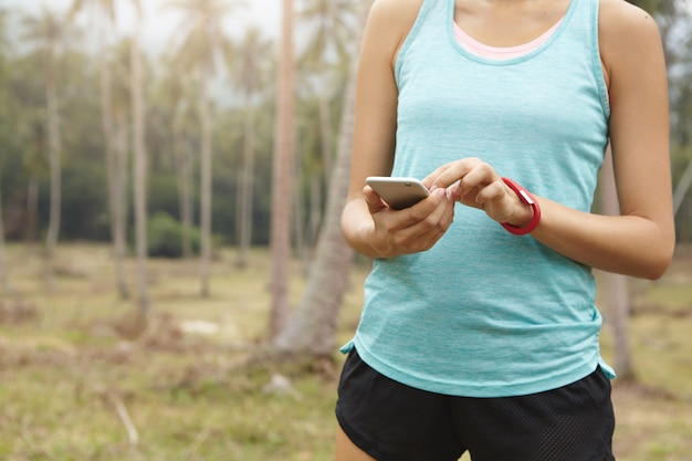 Midsection of female jogger in sportswear holding cell phone, using app fitness tracker for monitoring weight loss progress during cardio workout.