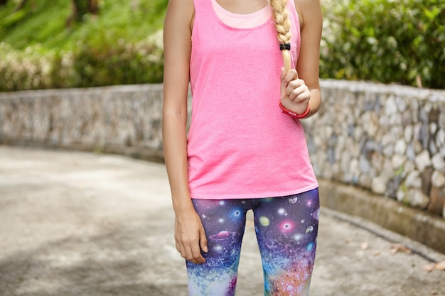 Midsection of fit blonde sportswoman dressed in pink tank top and space print leggings having rest outdoors, pulling her pigtail, standing in green park. young athletic girl relaxing during workout