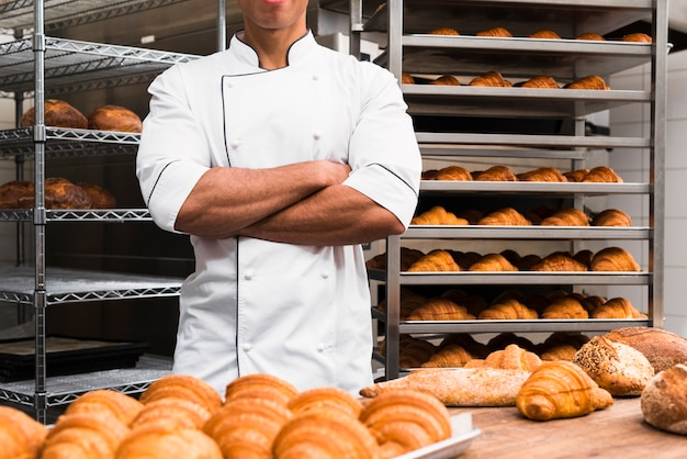 Midsection of a male baker with his arms crossed standing in bakery