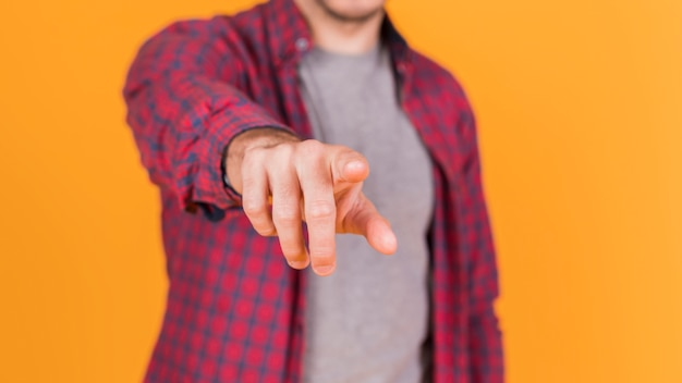 Midsection of a man pointing his finger toward the camera against an orange backdrop