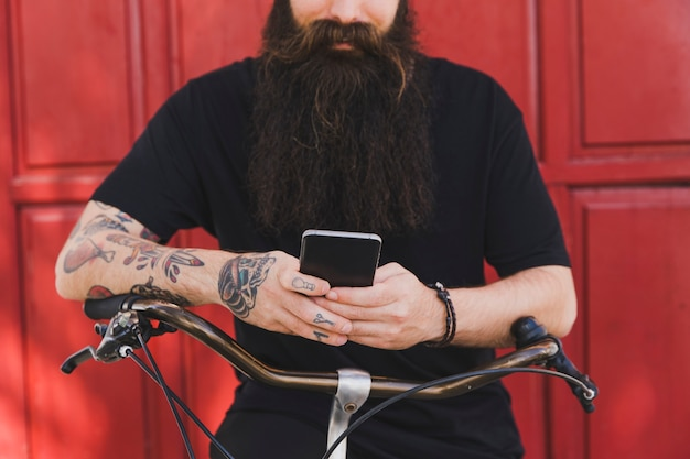 Midsection of a man sitting on bicycle against red door using mobile phone
