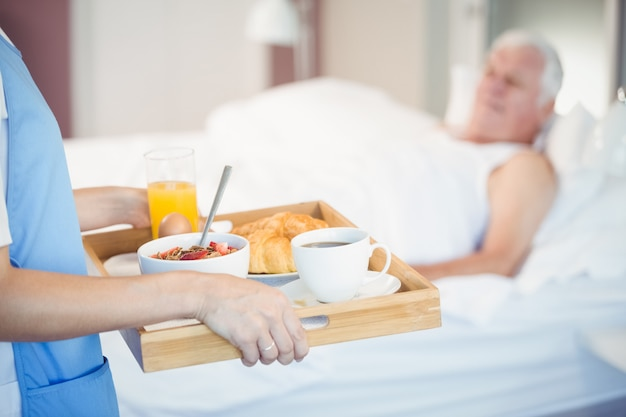 Midsection of nurse with breakfast in tray