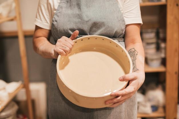 手で女性の陶芸家を示すセラミック容器の中央部