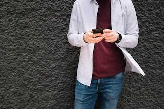 Midsection of a man leaning on wall using mobile phone