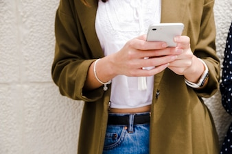 Midsection of a woman using mobile phone