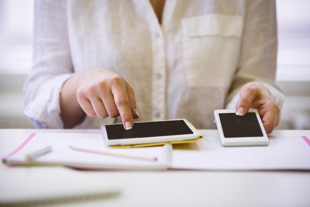 Животик бизнес-леди с беспроводными технологиями на столе в офисе