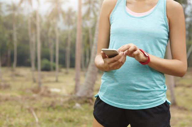 Бегунья в спортивной одежде держит мобильный телефон и использует фитнес-трекер для отслеживания прогресса потери веса во время кардиотренировки.