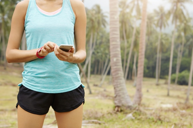 달리기 중 거리와 시간을 추적하기 위해 스마트 폰에서 실행중인 앱에 데이터를 입력하는 맞는 여성 러너의 중앙부.