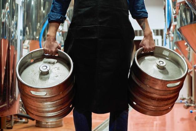 Живот работника завода по производству пива в фартуке, несущего две цистерны, во время движения перед камерой по рядам огромных стальных резервуаров