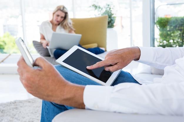 Животик человека с помощью планшета в то время как женщина держит ноутбук