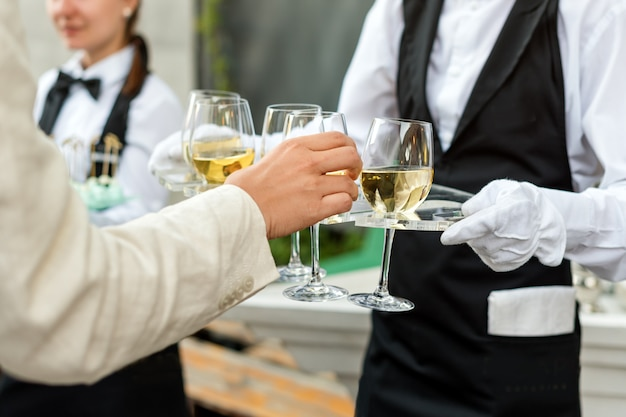Животик профессионального официанта в униформе, предлагающий вино во время фуршета, праздничного мероприятия или свадьбы. полные бокалы шампанского на подносе. кейтеринг на открытом воздухе, дежурный официант.