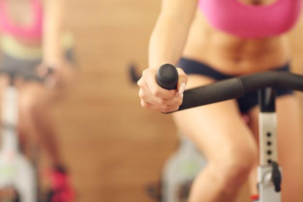 Живот спортивной группы женщин на занятии спиннингом