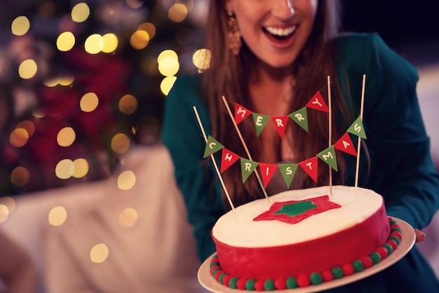家でクリスマスケーキを保持している女性の中央部