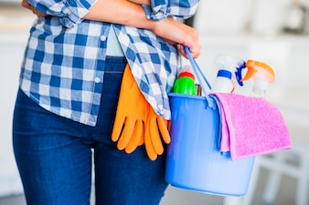 Midsection of woman's hand holding cleaning equipments in the bucket