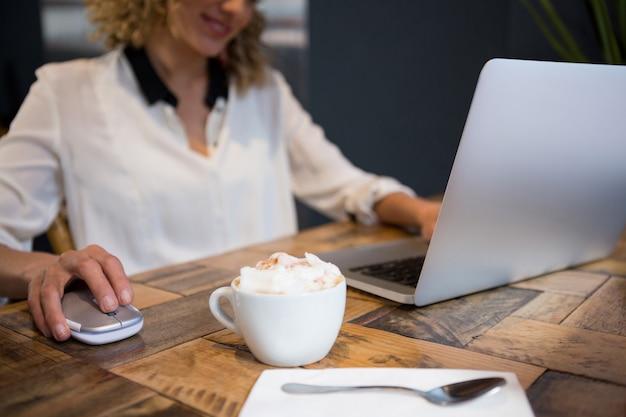 카페 테이블에 커피와 함께 노트북을 사용하는 여자의 중앙부