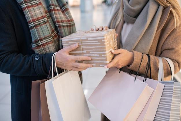 ショッピングモールでのクリスマスプレゼントを購入しながら紙袋とラップされたギフトボックスを保持しているカジュアルなカップルの中央