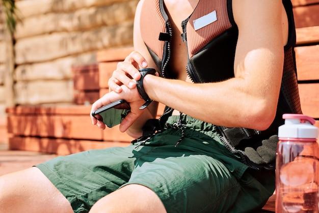 반바지와 안전 재킷을 입은 젊은 스포츠맨의 중간 부분은 나무 벤치에 앉아 화창한 날 휴식 시간에 시계를 보고 있습니다.