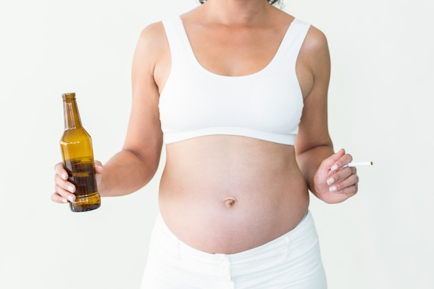 Midsection of pregnant woman holding cigarette and beer bottle against white background