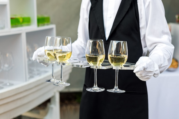 Midsection of professional waiter in uniform serving wine during buffet catering party, festive event or wedding. full glasses of champagne on tray. outdoor party catering service, waiter on duty.