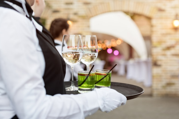 Midsection of professional waiters in uniform serving wine, cocktails and snacks during buffet catering party, festive event or wedding. full glasses of wine on tray. outdoor party catering service.