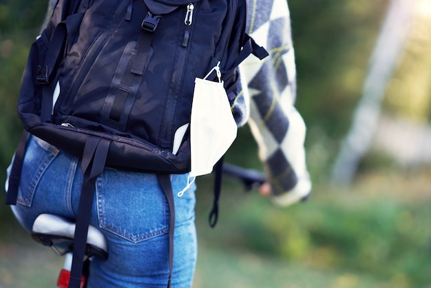Midsection of teenage girl biking to school with protective mask