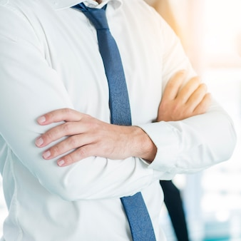 Midsection view of a businessman's folded arms