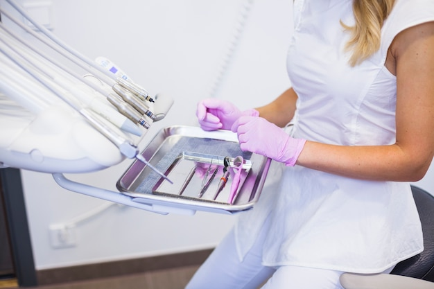 Midsection view of a dentist's hand arranging dental tools on tray