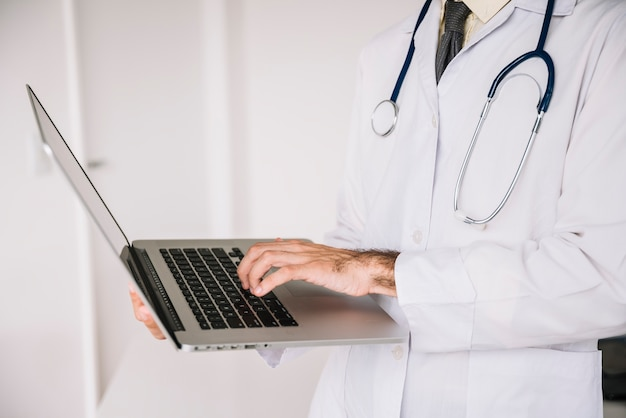 Midsection view of a doctor hand using laptop