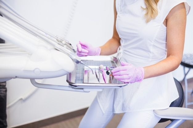 Midsection view of a female dentist with dental tools on tray