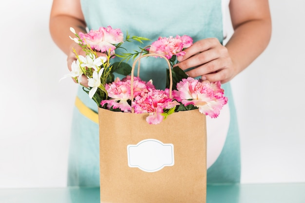 Midsection view of female florist with flower paper bag