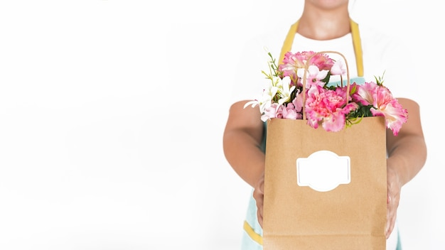 Midsection view of a florist hand holding paper bag full of flowers on white background
