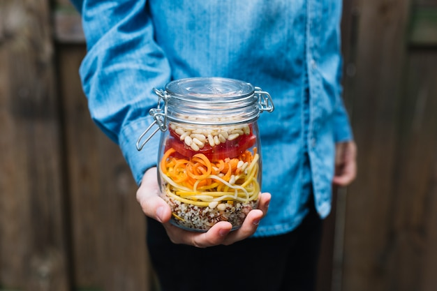 Midsection view of a human hand holding pasta salad in mason jar