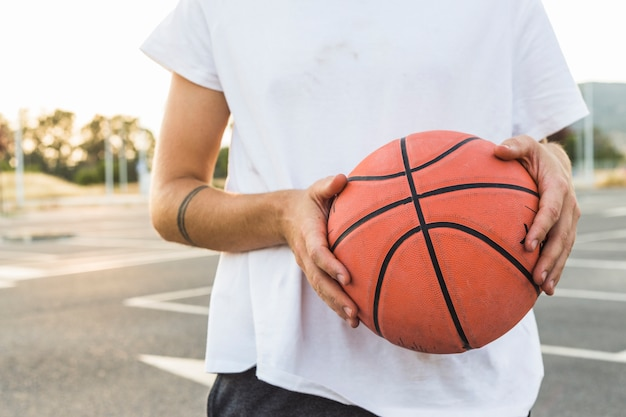Midsection view of a man holding basketball