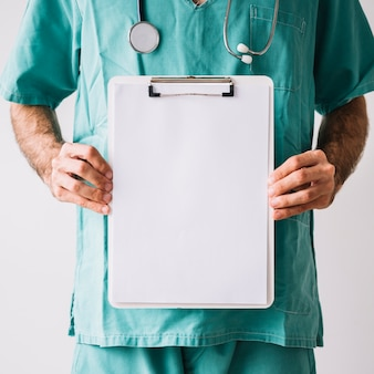 Midsection view of a male doctor holding clipboard with blank white papers
