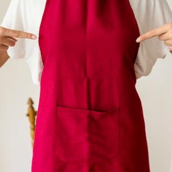 Вид в средней части женщины, указывающей пальцем на красный фартук