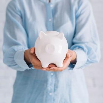 白いpiggybankを保持している女性の手の中央部の図