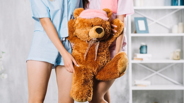 Midsection view of two female friends holding soft toy