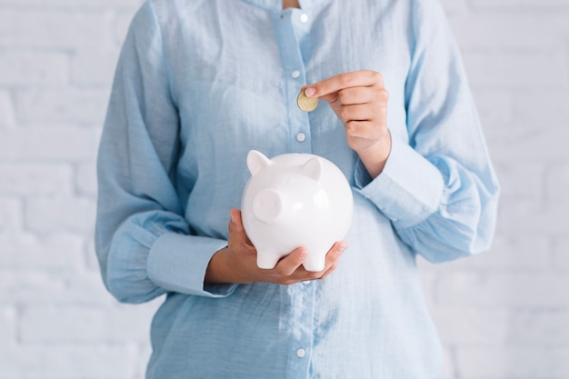 Midsection view of a woman's hand inserting coin in white piggybank