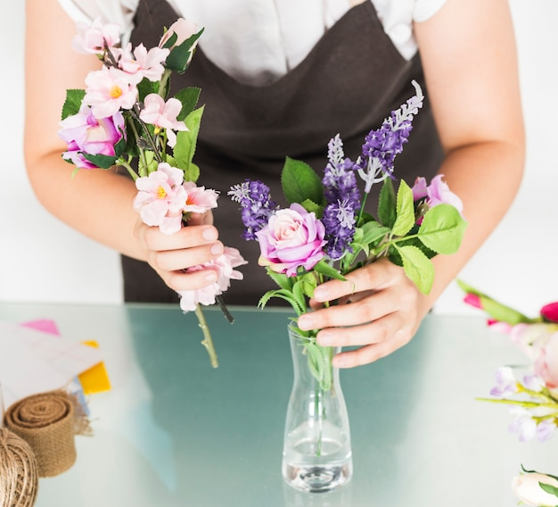 Midsection view of a woman's hand putting flowers in vase on glass desk