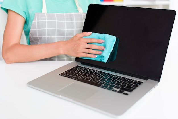 Midsection of woman in grey apron cleaning laptop screen at home