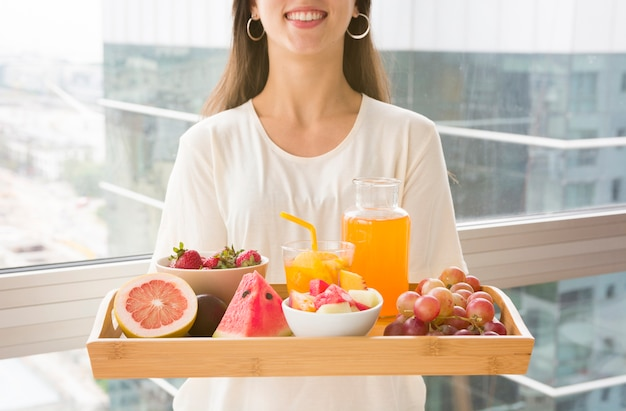 Midsection of a woman holding wooden tray with many fruits and juice