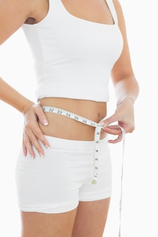 Midsection of woman measuring waist
