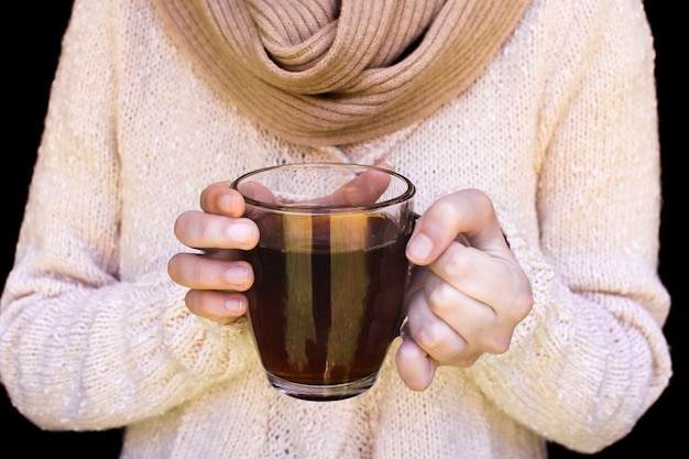 Midsection of a woman wearing woolen sweater holding glass cup of herbal tea