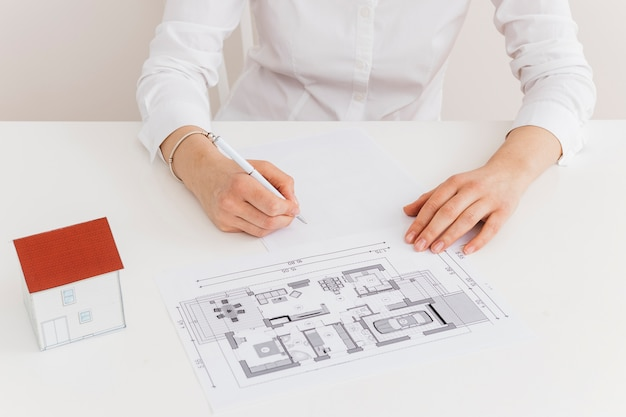 Midsection of woman working on house blueprint at desk in office