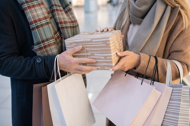 Midsection of young casual couple holding paperbags and wrapped giftbox while buying presents for christmas in the mall