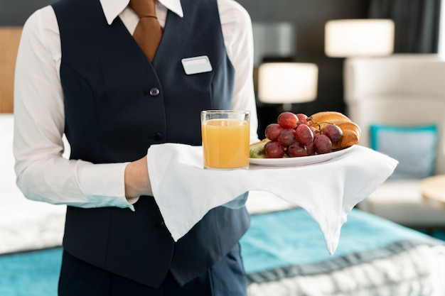 Midsection of young elegant female worker of hotel holding tray with breakfast while standing in front of camera against bed