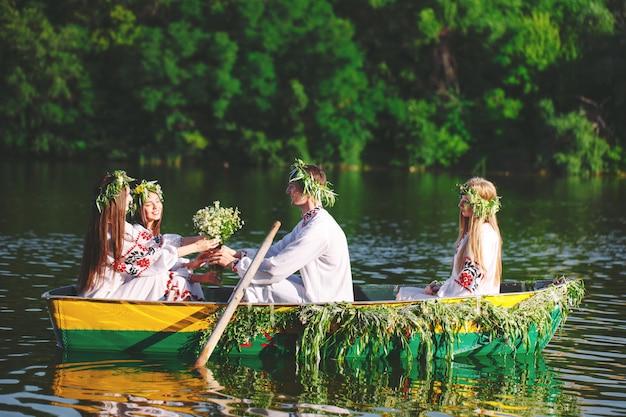 Середина лета. группа молодых людей в национальных костюмах плывет на лодке, украшенной листьями и наростами. славянский праздник ивана купалы.