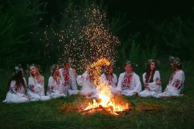 В летнюю ночь молодые люди в славянских одеждах сидят у костра.